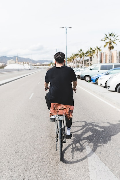 Vista posteriore di un uomo in sella alla bicicletta su strada dritta Foto Gratuite