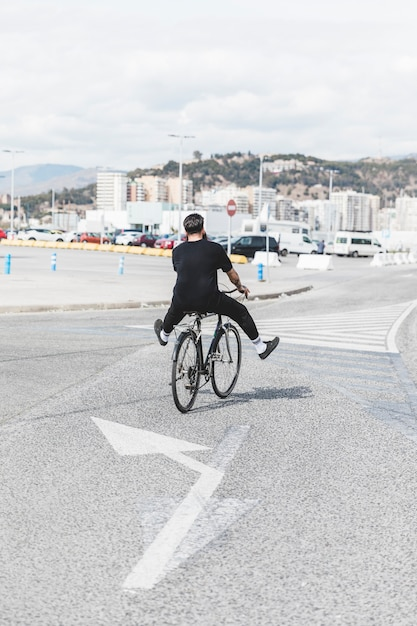 Vista posteriore di un uomo in sella alla bicicletta sulla strada Foto Gratuite