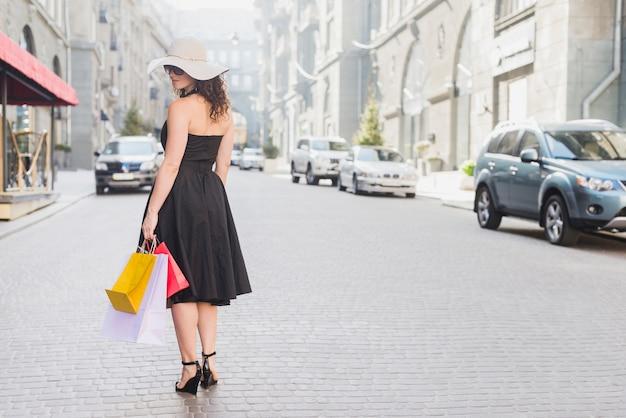 Vista posteriore di una donna con borse della spesa Foto Gratuite