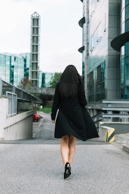 Vista posteriore di una donna d'affari che cammina sulla strada Foto Gratuite
