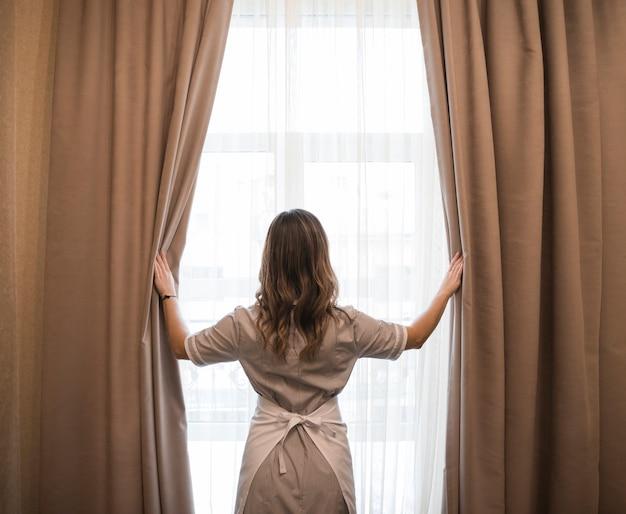 Vista posteriore di una giovane cameriera che apre le tende nella camera d'albergo Foto Gratuite
