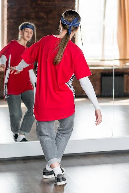 Vista posteriore di una giovane donna che balla davanti allo specchio Foto Gratuite