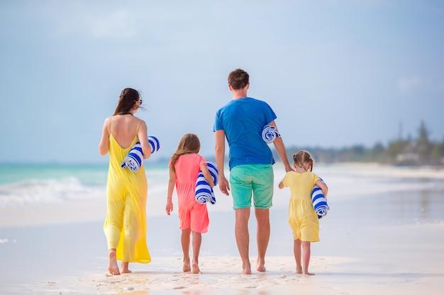 Vista posteriore di una giovane famiglia sulla spiaggia tropicale Foto Premium