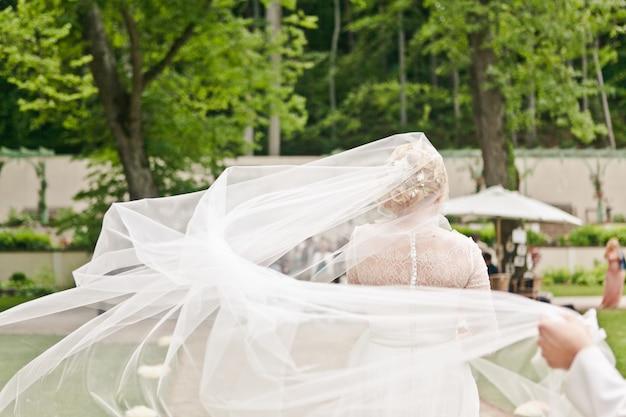 Vista posteriore di una sposa in un abito di pizzo con un velo che fluttua nel vento viene inviato al luogo della cerimonia di matrimonio Foto Premium