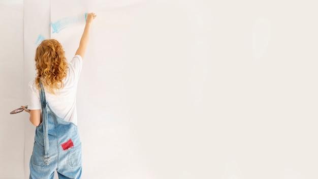 Vista posteriore donna che dipinge un muro Foto Gratuite