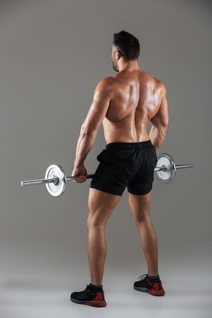 Vista posteriore integrale di un forte bodybuilder maschio senza camicia Foto Gratuite