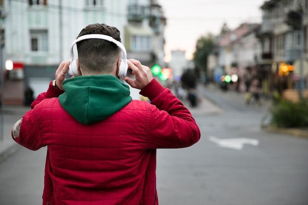 Vista posteriore ragazzo con cuffie e vestiti caldi Foto Gratuite