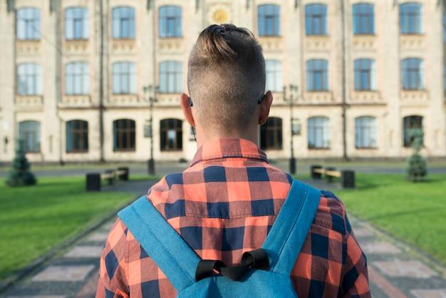 Vista posteriore vicino adolescente che cammina al liceo Foto Gratuite