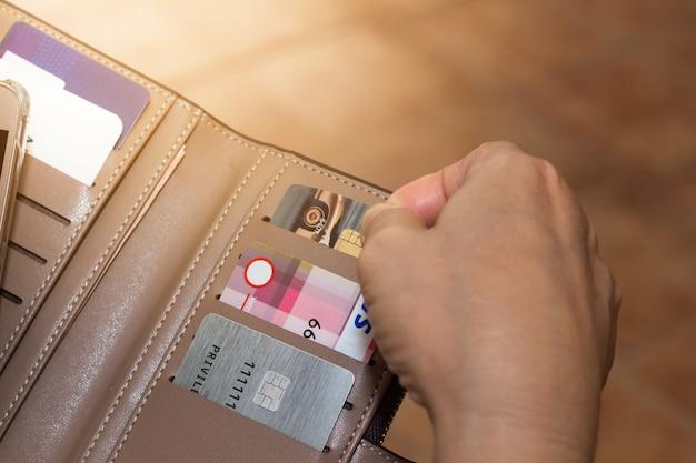 Vista potata del colpo delle mani femminili che selezionano le carte di credito dal suo portafoglio Foto Premium