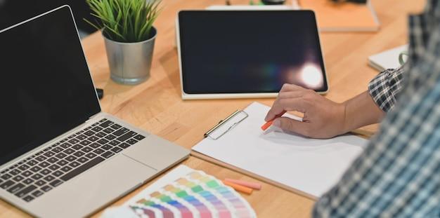 Vista potata di giovane graphic designer che attinge la carta Foto Premium