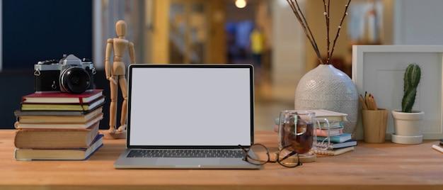 Vista ravvicinata dell'area di lavoro con mock up laptop, libri, forniture e decorazioni sulla scrivania in legno nella stanza dell'ufficio Foto Premium