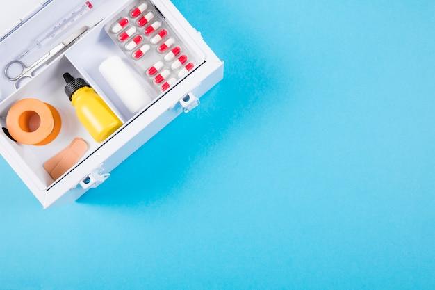 Vista sopraelevata della cassetta di pronto soccorso medica su fondo blu Foto Gratuite