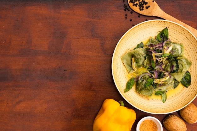 Vista sopraelevata della pasta verde dei ravioli con peperone dolce e pane gialli su superficie di legno Foto Gratuite