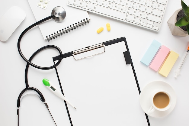 Vista sopraelevata dello scrittorio medico con la tazza di caffè e le note adesive sulla tavola Foto Gratuite