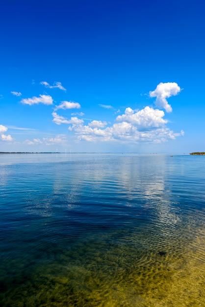 Vista sul mare con soffici nuvole bianche e mulini a vento in lontananza Foto Premium