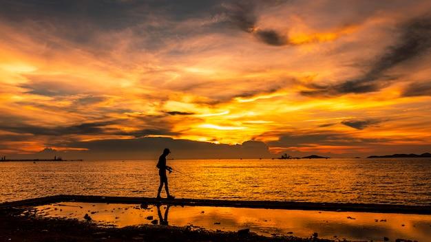 Vista sul mare crepuscolare il tramonto e l'oro chiaro con la priorità alta della siluetta del pescatore sull'isola in tailandia Foto Premium