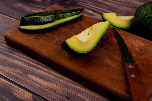 Vista superiore affettato avocado con coltello sul tagliere sul tavolo di legno Foto Gratuite