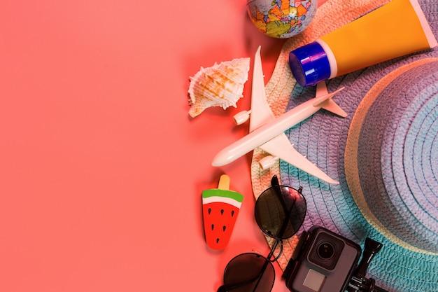 Vista superiore degli accessori del viaggiatore, della foglia di palma tropicale e dell'aeroplano sul rosa Foto Premium