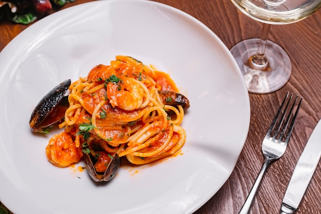 Vista superiore degli spaghetti dei frutti di mare con la salsa al pomodoro e il prezzemolo delle cozze gamberetti Foto Gratuite