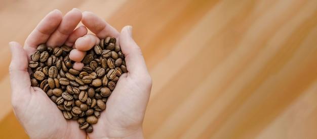 Vista superiore dei chicchi di caffè della tenuta di barista in mani in forma di cuore con lo spazio della copia Foto Gratuite