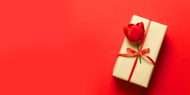 Vista superiore dei contenitori di regalo avvolti della molla con i nastri rossi sul piano d'appoggio rosso. Foto Premium