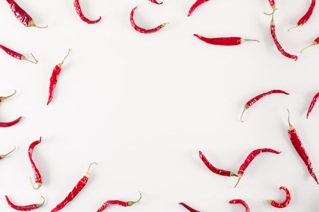 Vista superiore dei peperoncini secchi rossi con lo spazio della copia su superficie bianca Foto Gratuite