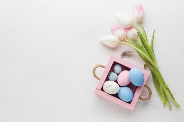 Vista superiore dei tulipani con le uova di pasqua e lo spazio della copia Foto Gratuite