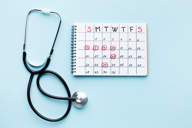 Vista superiore del calendario e dello stetoscopio di trattamento medico Foto Gratuite