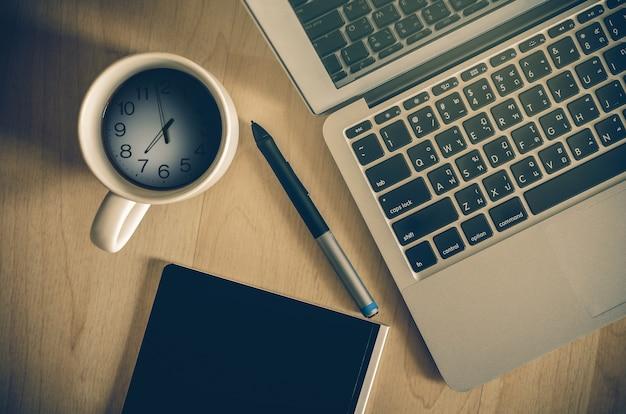 Vista superiore del computer portatile, blocco note e tazza di caffè che ha mostrato il tempo Foto Premium