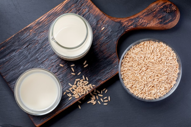 Vista superiore del latte di avena sano in bottiglia di vetro e semi di avena e vetro sulla ciotola di vetro Foto Premium