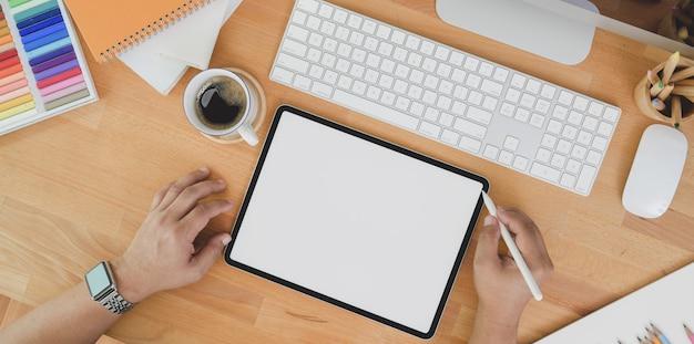 Vista superiore del progettista professionista che pubblica il suo lavoro sul tablet sulla tavola di legno Foto Premium