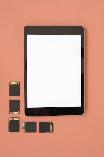 Vista superiore del tablet digitale vuoto con schede di memoria su sfondo arancione Foto Gratuite