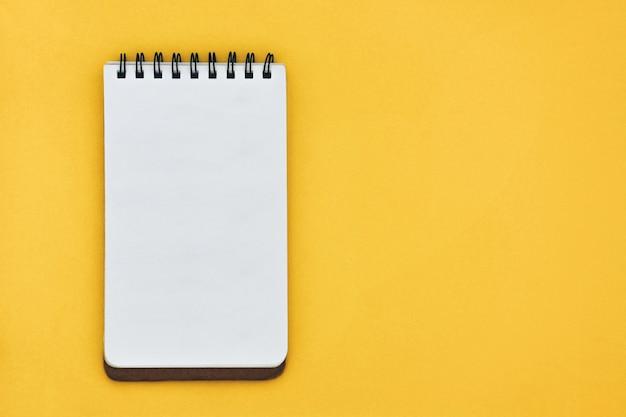 Vista superiore del taccuino aperto vuoto su giallo Foto Premium