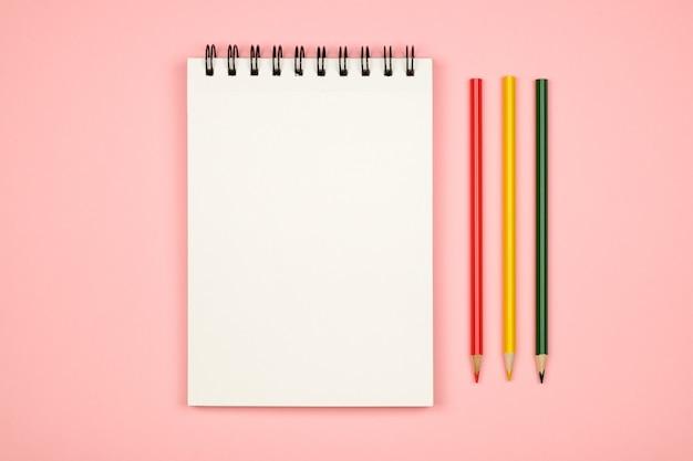 Vista superiore del taccuino in bianco con le matite colorate Foto Premium