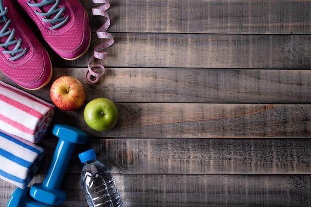 Vista superiore dell'attrezzatura dell'atleta sulla tavola di legno scura. concetto di stile di vita sano Foto Premium