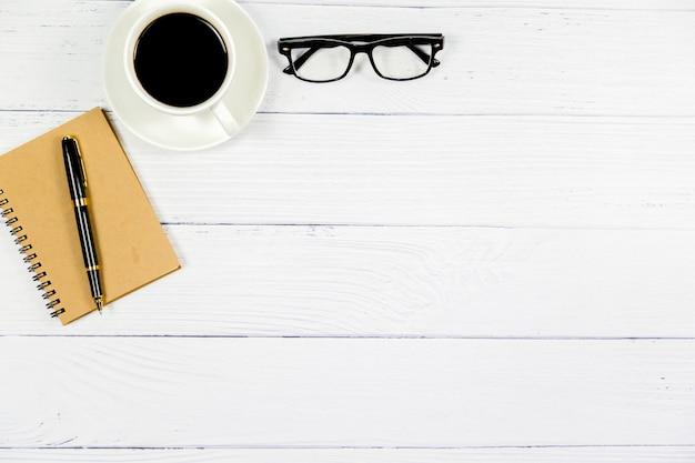 Vista superiore dell'ufficio, scrittorio bianco di legno con caffè, vetri, penna, concetto di affari. Foto Premium