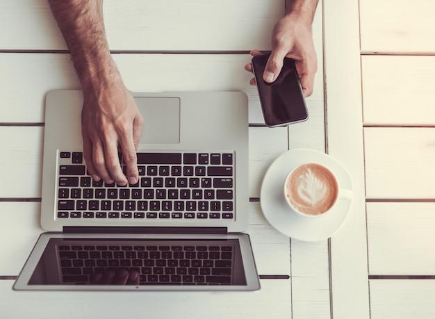 Vista superiore dell'uomo d'affari che per mezzo di un computer portatile e di uno smart phone. Foto Premium