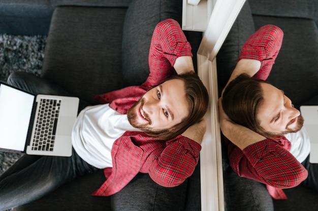 Vista superiore dell'uomo rilassato felice che per mezzo del computer portatile a casa Foto Gratuite