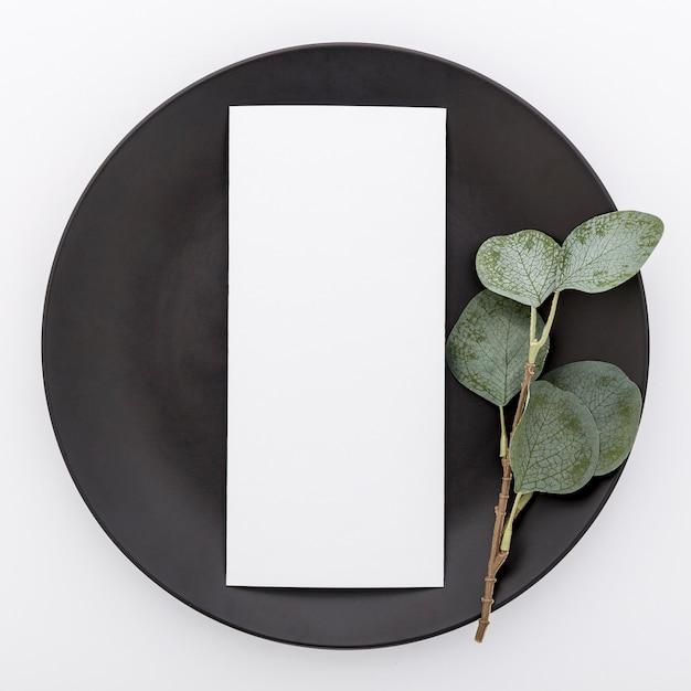 Vista superiore della carta in bianco del menu sul piatto con la pianta Foto Gratuite