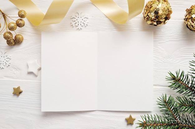 Vista superiore della cartolina d'auguri di natale e stella d'oro, flatlay su priorità bassa bianca Foto Premium