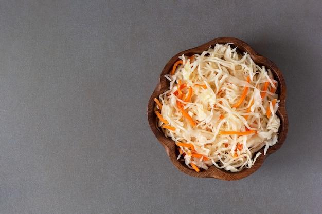 Vista superiore della ciotola di legno della carota e dei crauti su fondo neutrale. Foto Premium
