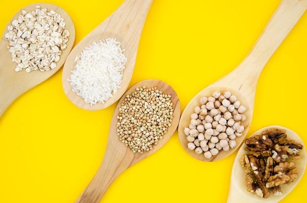 Vista superiore della composizione sana nei cucchiai dei semi Foto Gratuite