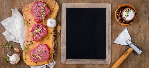 Vista superiore della lavagna con carne e aglio Foto Gratuite