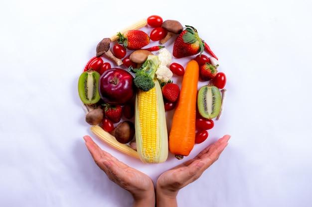 Vista superiore della mano della donna con gli ortaggi freschi e la frutta su libro bianco. giornata mondiale dell'alimentazione o giornata vegetariana. Foto Premium