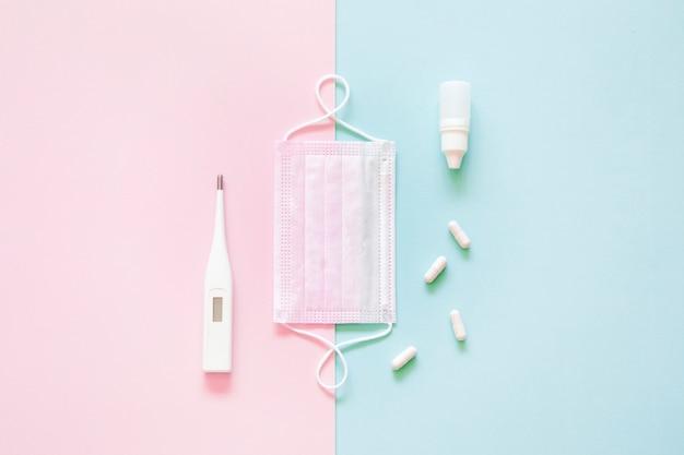 Vista superiore della maschera medica, pillole e termometro su sfondo rosa e verde. Foto Gratuite