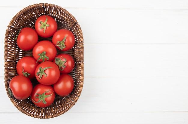 Vista superiore della merce nel carrello dei pomodori dalla parte di sinistra e dalla superficie bianca con lo spazio della copia Foto Gratuite
