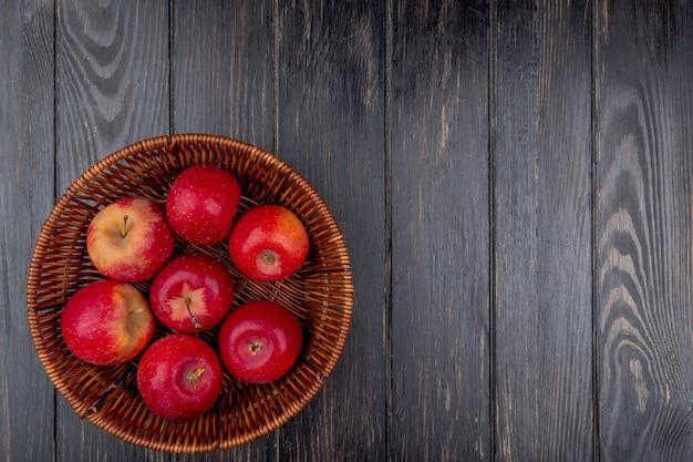 Vista superiore della merce nel carrello rossa delle mele su fondo di legno con lo spazio della copia Foto Gratuite