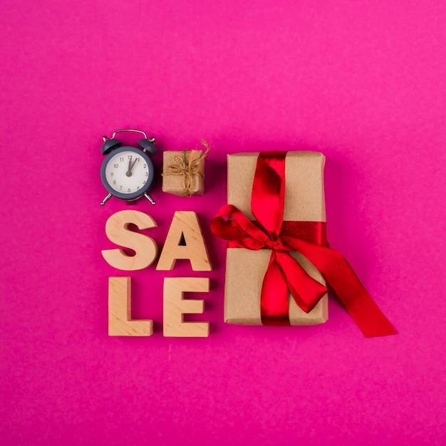 Vista superiore della parola di vendita e regali con backkground rosa Foto Gratuite