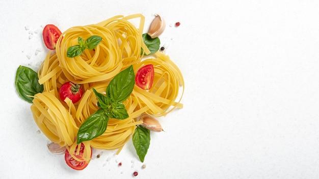 Vista superiore della pasta tagliatele con basilico e pomodori con spazio di copia Foto Gratuite