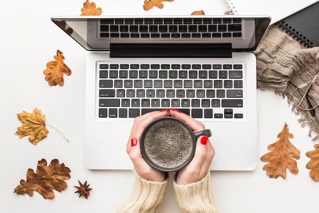 Vista superiore della persona che tiene la tazza di caffè con il computer portatile Foto Gratuite